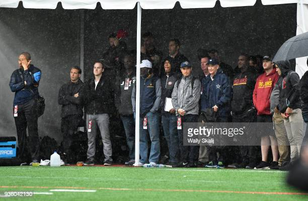NFL scouts and USC assistants take cover from the rain as they watch quarterback Sam Darnold throw during pro day at USC Wednesday