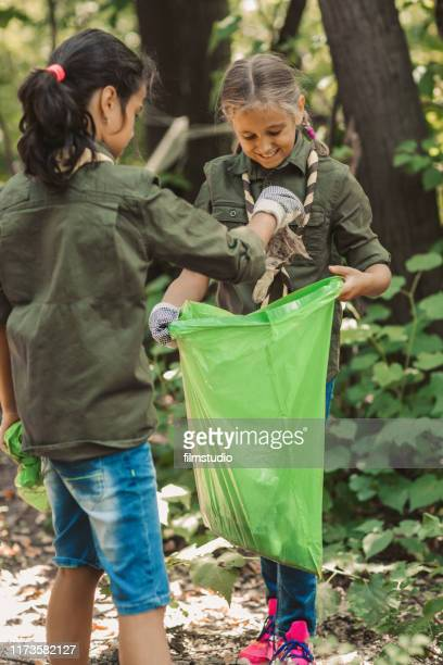 scouts cleaning local forest - girl scout stock pictures, royalty-free photos & images