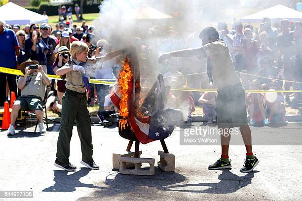 Scouts from Boy Scouts of America's Troop 775 retire a worn American flag during a ceremony before the start of the 47th Annual Westlake Village 4th...
