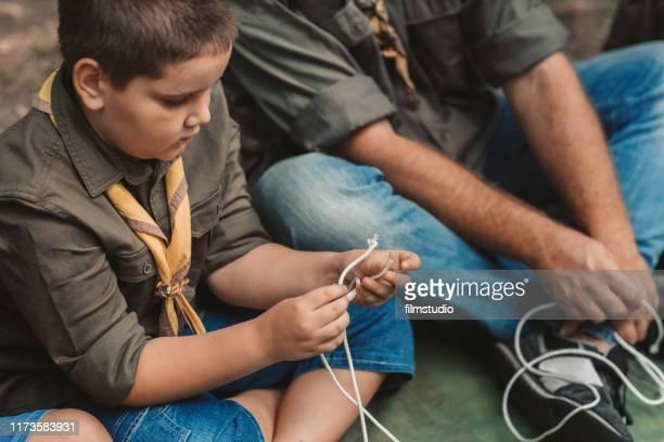 pfadfinder lernen, den knoten zu knüpfen - pfadfinder stock-fotos und bilder