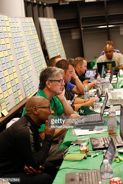 Scouts of the Oakland Athletics check their computer in the Athletics draft room during the first day of the 2015 MLB Draft at Oco Coliseum on June 8...