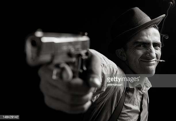 Scowling man pointing a gun on a black background.