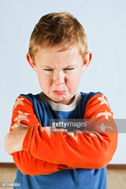 Scowling pre-school boy with folded arms has a tantrum
