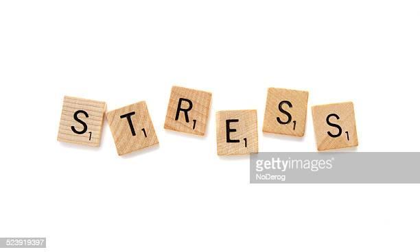 Scrabble letter tiles spelling the word STRESS