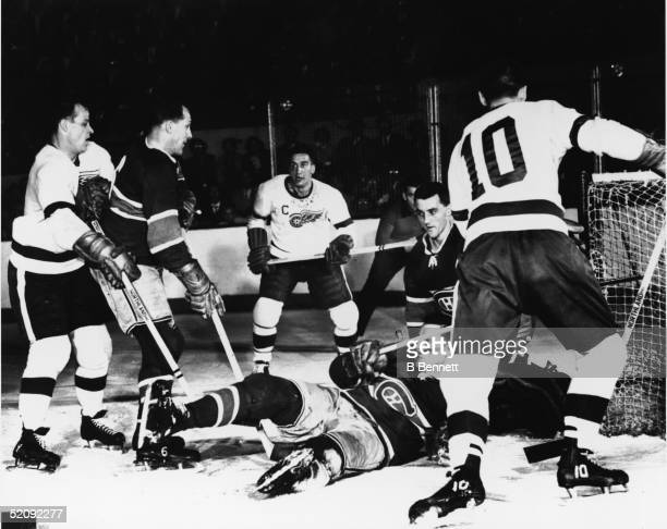 A scramble in front of the net during a game between the Detroit Red Wings and the Montreal Canadiens mid 1950s Players are from left Red Wing Gordie...