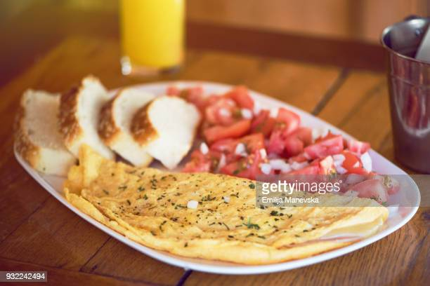 Scrambled eggs in a plate and tomatoes