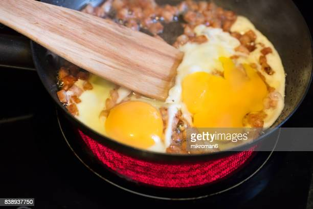 scrambled eggs with beacon and sausage on fried pan for breakfast on hot electric hob - electric stove burner stock pictures, royalty-free photos & images
