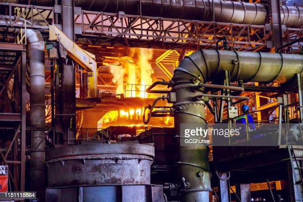 scrap metal being poured into an electric arc furnace at a steel factory - electric arc furnace stock photos and pictures