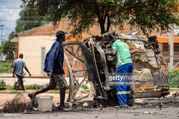Scrap metal collectors salvages sellable parts from a car shell burnt during the three days protests in Emakhandeni township in Bulawayo on January...