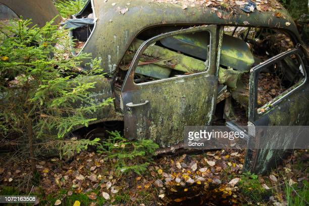 scrap trucks on the abandoned junkyard kyrkö mosse outside ryd in southern sweden - obsolete stock pictures, royalty-free photos & images