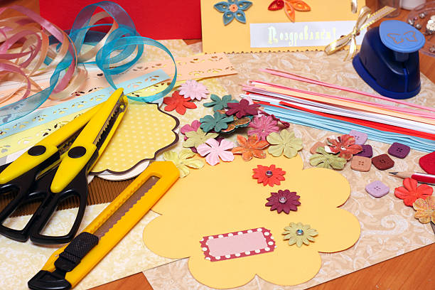 Scrapbooking supplies and tools scattered on table