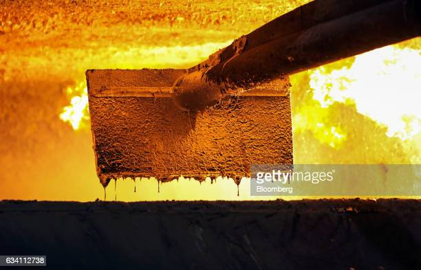 A scraper removes impurities from liquid aluminum in a furnace at the Lochaber aluminum smelter operated by Liberty House Group in Fort William UK on...