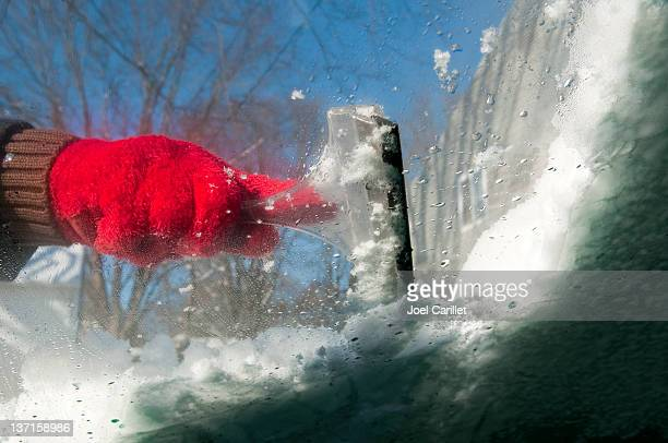 Scraping icy windshield in winter
