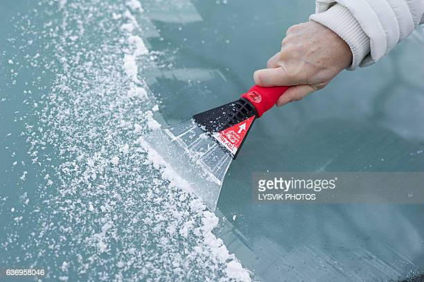 scraping snow and ice from the car windscreen - scraping stock photos and pictures