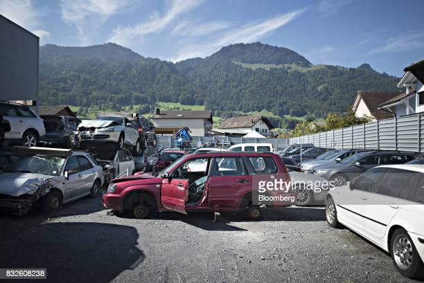 Scrapped automobiles stand stacked in the yard of the Autoverwertung Zimmermann GmbH scrapyard in Reichenburg Switzerland on Monday Aug 14 2017...