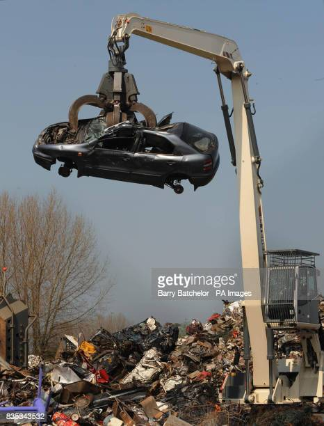 A scrapped car is lifted towards the crusher at Phelps Bros Ltd iron and metal recycling in Gloucester ahead of Wednesday's budget