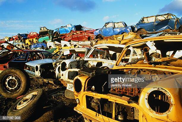 scrapped cars piled up in yard - scrapped cars stock photos and pictures