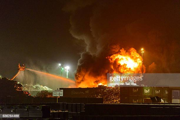 scrapyard fire in an industrial area at night - junkyard stock photos and pictures