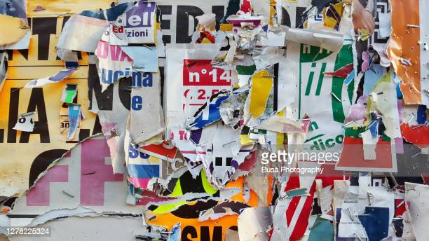scratched layers of posters and placards on a street wall - torn stock pictures, royalty-free photos & images