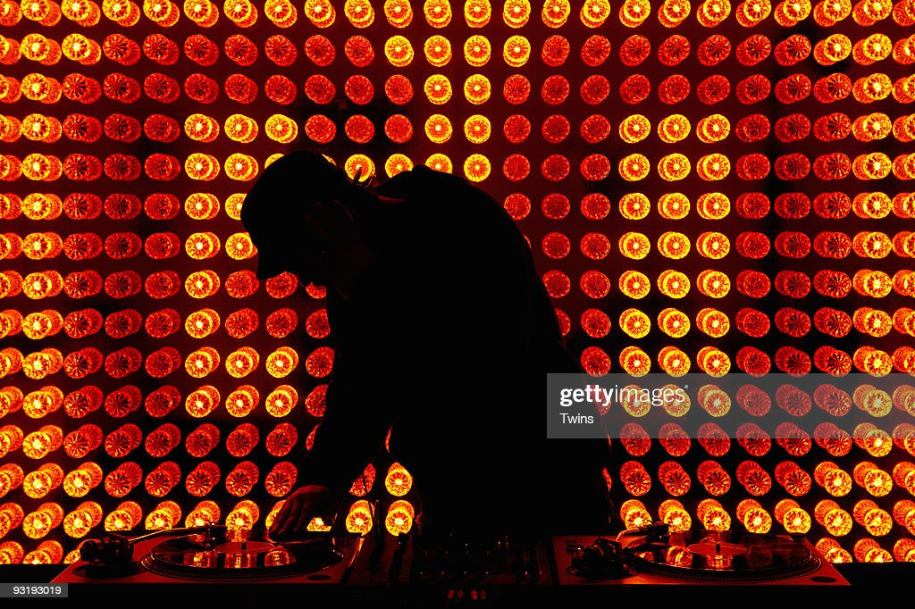 A DJ scratching a record in a nightclub : Stock Photo