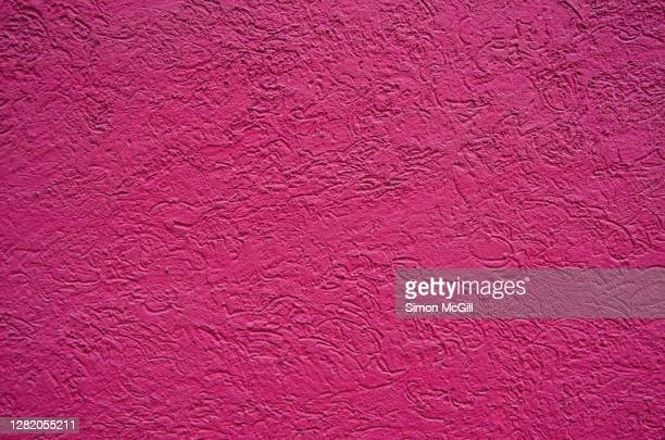 scratchy textured building exterior stucco wall painted bright mexican hot pink - ショッキングピンク ストックフォトと画像