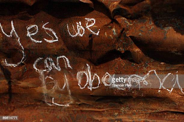 A scrawled slogan of US President Barack Obama who is part Kenyan is displayed on the wall of a shack in the Kibera slum August 15 2009 in Nairobi...