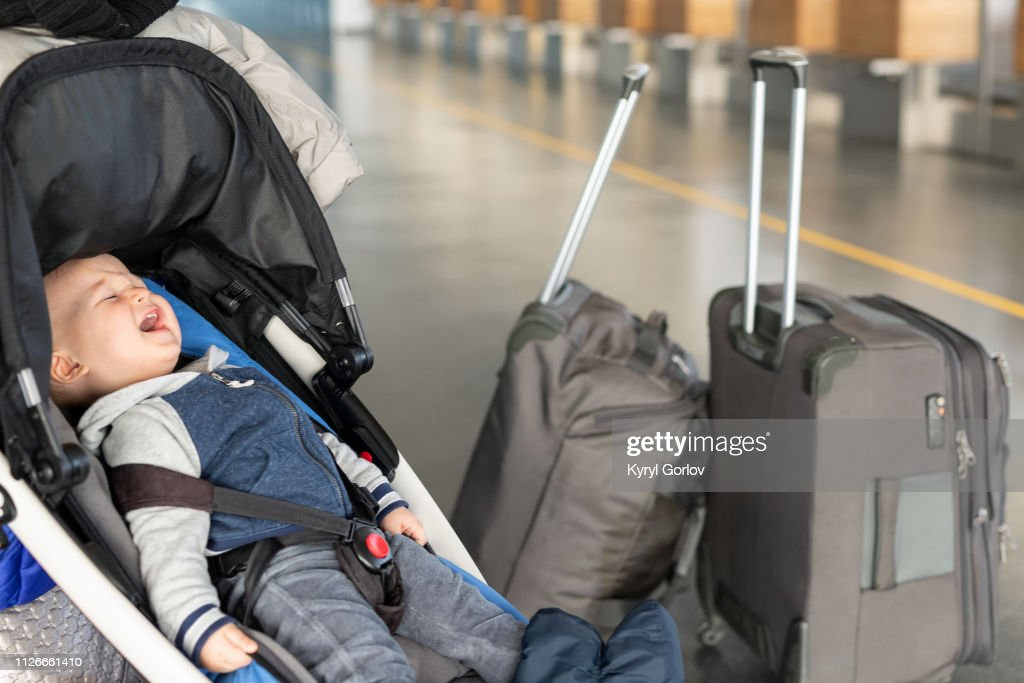 Screaming baby boy sitting in stroller near luggage at airport terminal. Child in carriage near check-in desk counter. Children tears , panic and hysterics. Travelling with small children concept : Stock Photo