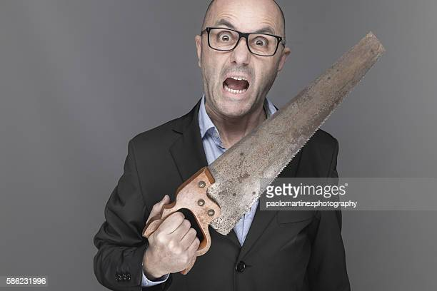 Screaming businessman holding saw
