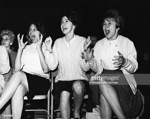 Screaming Fans overcome with Beatlemania attend a concert by the rock and roll band 'The Beatles' in 1964