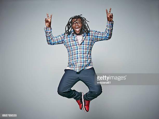 Screaming man with dreadlocks jumping in the air while showing victory signs