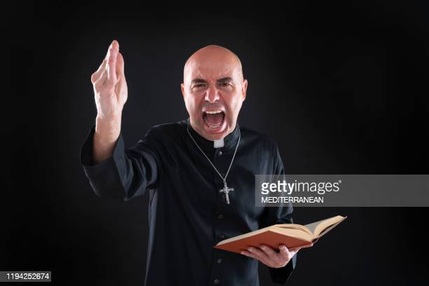 screaming priest in sermon holding bible hand angry - vicar stock pictures, royalty-free photos & images