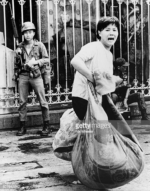 Screaming refugee woman flees her home with bundled possessions during Viet Cong attack on Saigon's Chinatown during the Mini Tet Offensive in...