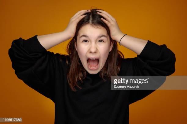 両手に頭を抱える黒いスウェットシャツでティーンエイジャーを叫ぶ - 手を顔にやる ストックフォトと画像