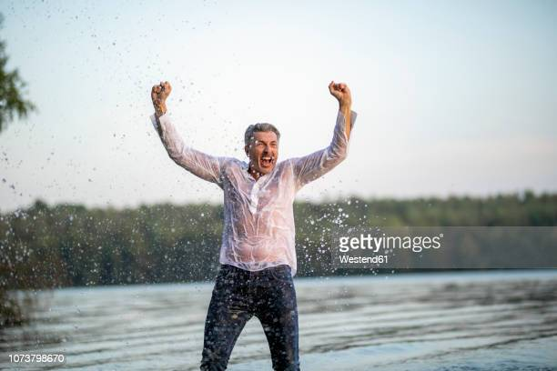 screaming wet mature man at lake - wet stock pictures, royalty-free photos & images