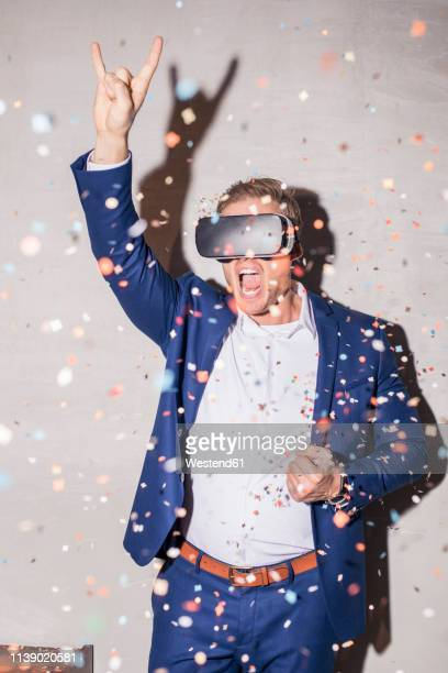 screaming young man man with virtual reality glasses standing in between confetti shower at a party - flying solo after party bildbanksfoton och bilder