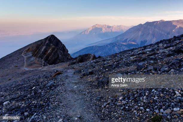 Scree-covered trail to Mount Borah / Borah Peak in Lost River Range, highest mountain in Idaho, smoky sunrise in September