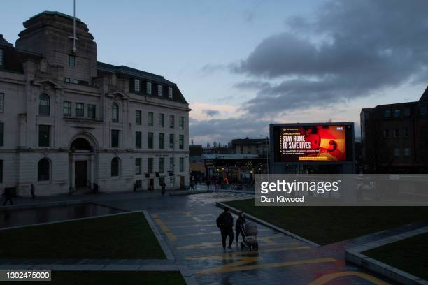 Screen broadcasts public service announcements on February 16, 2021 in East London, United Kingdom. A 'roadmap' for ending the current restrictions...