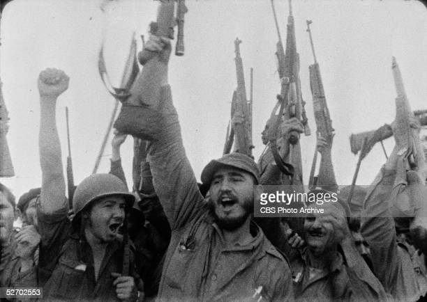 Screen capture of Cuban guerilla leader and future dictator Fidel Castro and associates as they cheer and raise their weapons and fists in the air on...