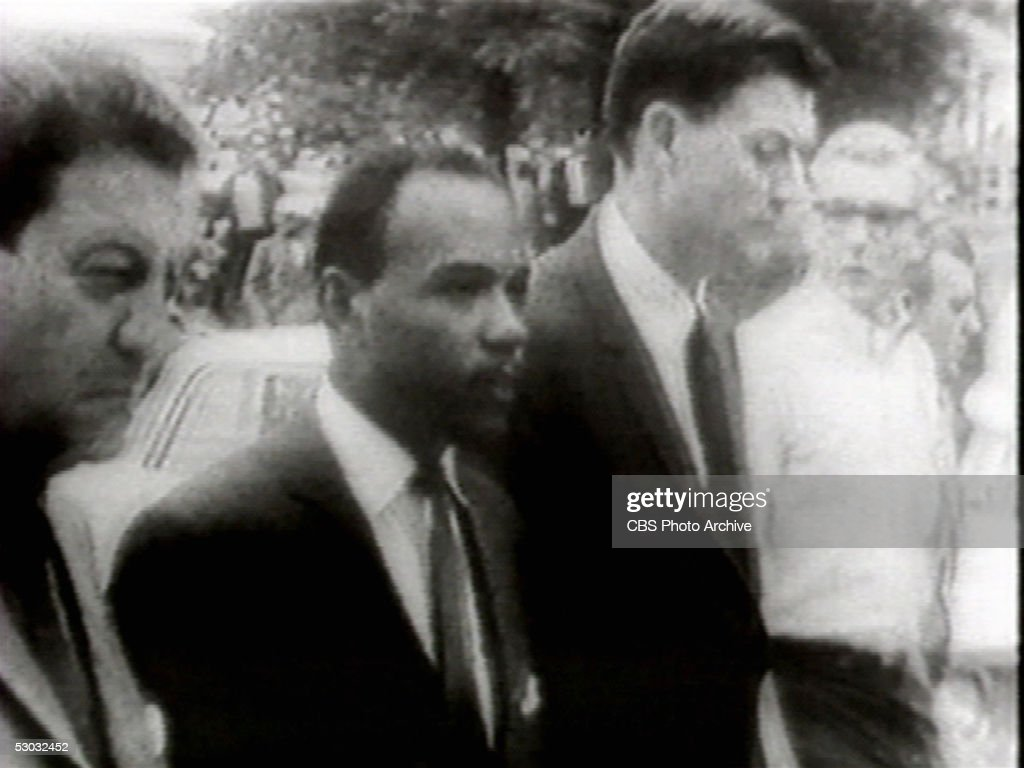 Screen capture shows American college student James Meredith (second from left), accompanied by US Department of Justice attorney John Doar (third from left), as he is escorted by federal marshals to become the first black student to register at the University of Mississippi after riots on campus the night before left two students dead and 160 marshals injured, Oxford, Mississippi, October 1, 1962. Meredith had been granted admission the previous year, but Mississippi governor Ross Barnett had ordered state troopers to bar his entrance and personally stood in Meredith's way. The US Supreme Court upheld Meredith's right to attend the university in its September 10, 1962, ruling, and Attorney General Robert F. Kennedy and President John F. Kennedy ordered federal troops to protect Meredith during his enrollment.