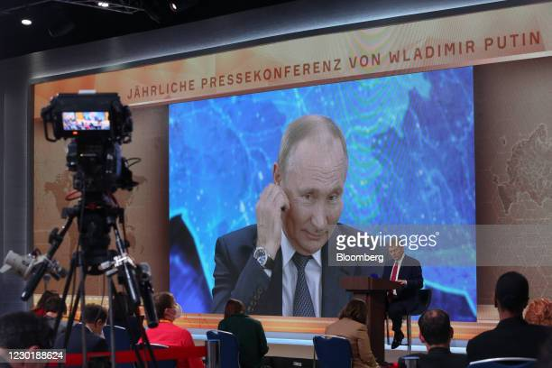 Screen displays a live broadcast of Vladimir Putin, Russia's President, delivering his annual news conference, at the Crowne Plaza World Trade Centre...