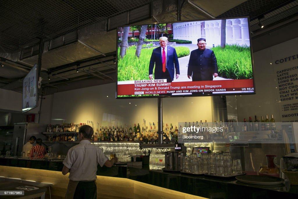 A screen displays a news broadcast of U S  President Donald