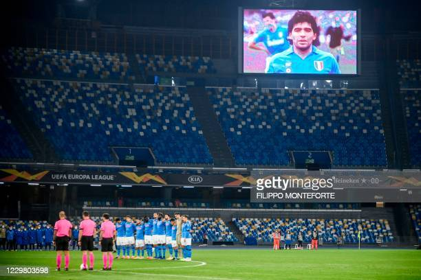 Screen displays a photo of late Argentinian football legend Diego Maradona as players hold a minute of silence in homage to Maradona prior to the...