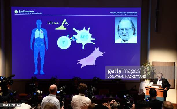 A screen displays a portrait of James P Allison and an illustration of his field of research during the announcement of the winners of the 2018 Nobel...