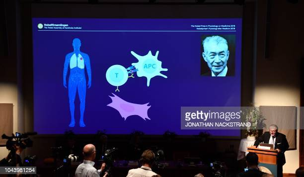 A screen displays a portrait of Tasuku Honjo and an illustration of his field of research during the announcement of the winners of the 2018 Nobel...