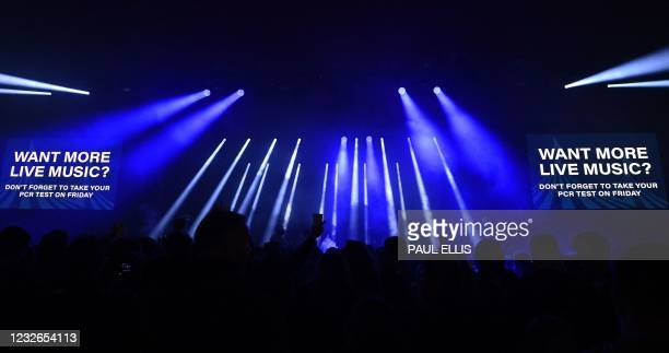 Screen displays a sign as concert-goers dance to music at the venue for the latest event in the government's Events Research programme, a live music...