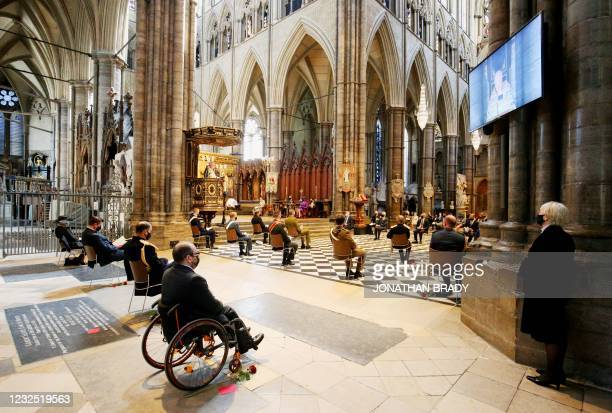 Screen displays an image of the Dean of Westminster David Hoyle as he delivers a reading during a service of commemoration and thanksgiving to mark...
