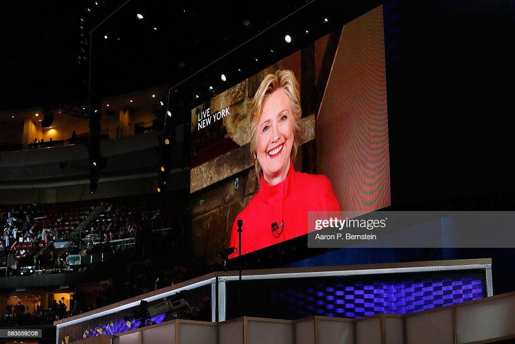 A screen displays Democratic presidential candidate Hillary Clinton delivering remarks during the evening session on the second day of the Democratic National Convention at the Wells Fargo Center, July 26, 2016 in Philadelphia, Pennsylvania. Democratic presidential candidate Hillary Clinton received the number of votes needed to secure the party's nomination. An estimated 50,000 people are expected in Philadelphia, including hundreds of protesters and members of the media. The four-day Democratic National Convention kicked off July 25.