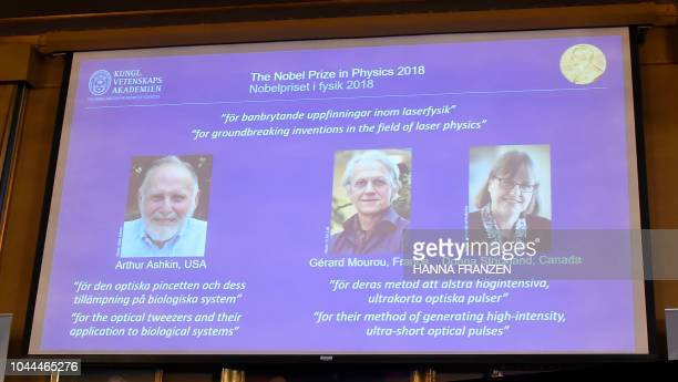 A screen displays portraits of Arthur Ashkin of the United States Gerard Mourou of France and Donna Strickland of Canada during the announcement of...
