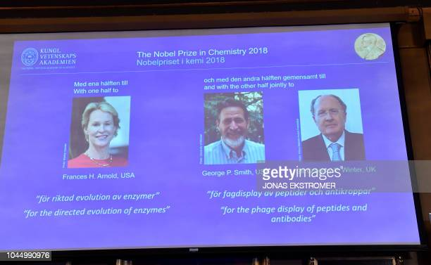 A screen displays portraits of Frances H Arnold of the United States George P Smith of the United States and Gregory P Winter of Great Britain during...