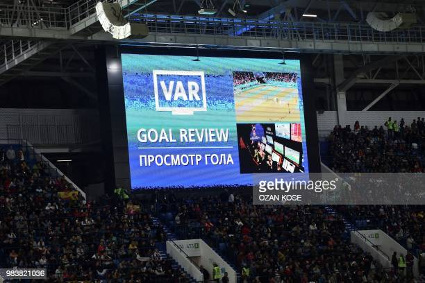 A screen displays the VAR goal review confirming Spain's second goal during the Russia 2018 World Cup Group B football match between Spain and...